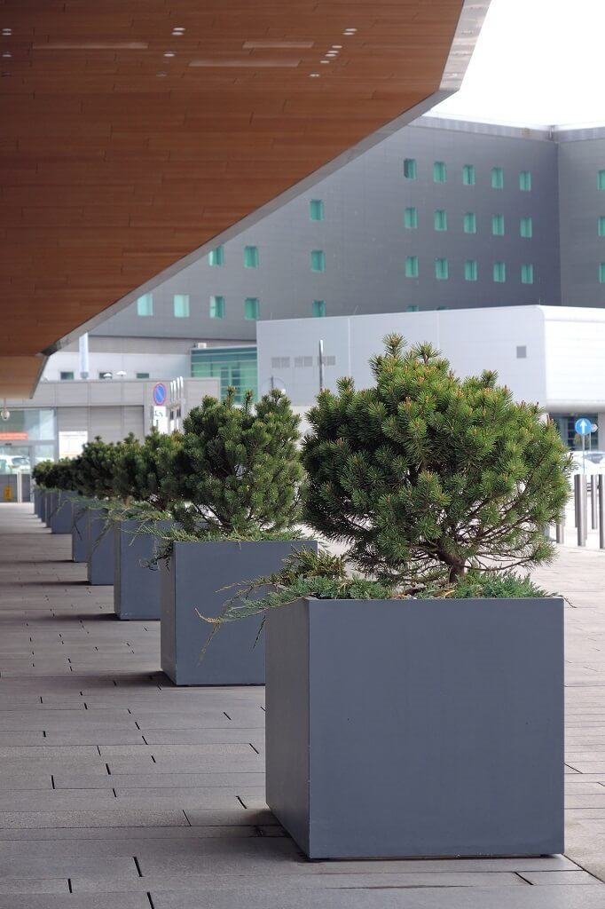 large polymer concrete planters on front of hotel